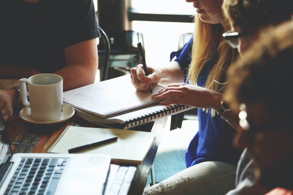 Mensen zitten naast elkaar aan een tafel. Voor hun ligt een laptop en een schrift. Het is een bijeenkomst waarbij er vergaderd wordt.