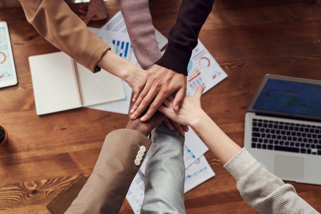 Zes personen staan in een cirkel en leggen hun rechterhand op elkaar, daarmee wordt teambuilding geïllustreerd en staat de afbeelding symbool voor de introductiedag van JongPIT voor nieuwe teamleden